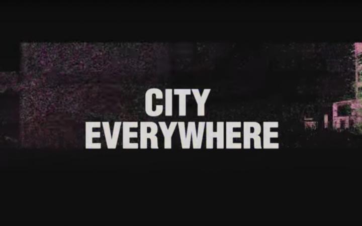 Der Schriftzug »City Everywhere« vor einem schwarzen Hintergrund mit Industrie-Gebäude.