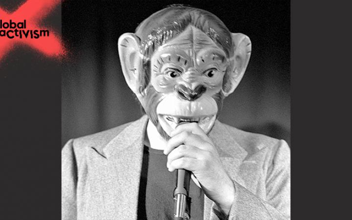A man with a monkeymask speaks into a microphone