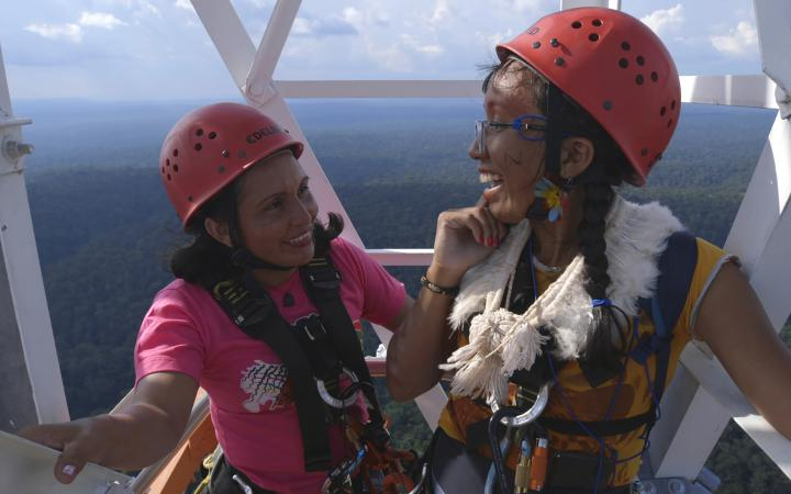 Two women can be seen standing high up on a tower. They wear safety helmets and laugh. In the background you can see forest up to the horizon.
