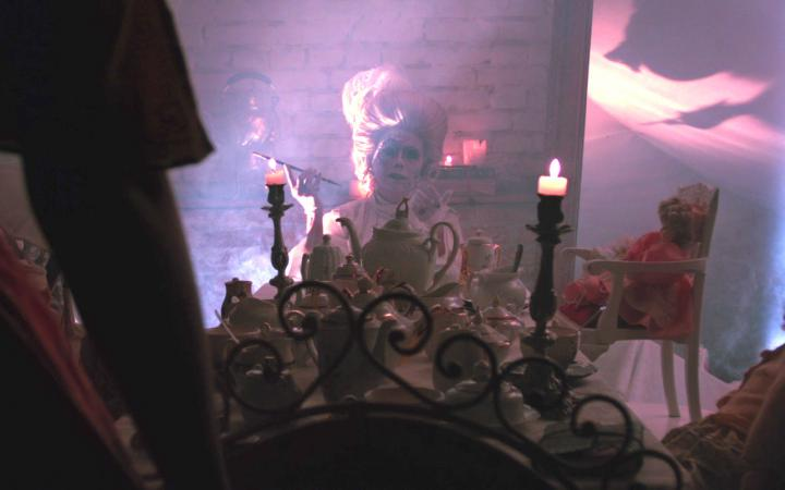 A smoking person is sitting in a room with stone walls. She is wearing a wig from the 18th century, is heavily made up and sits at a table with a long candle burning on it. Around the table are dolls.