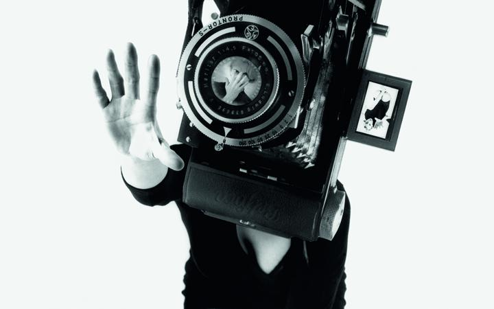 The black and white photo shows a woman in a black mini dress on her knees. Her face is covered by an oversized camera.