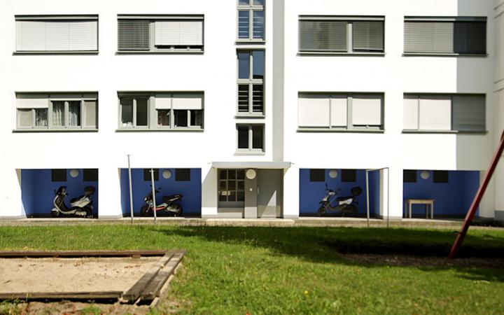 Zu sehen ist ein großes Weiße Gebäude mit einer Galerie im Erdgeschoss, deren Wände blau gestrichen sind. Das Gebäude befindet sich in der Dammerstocksiedlung in Karlsruhe, die aus der Bauhaus Zeit stammt.