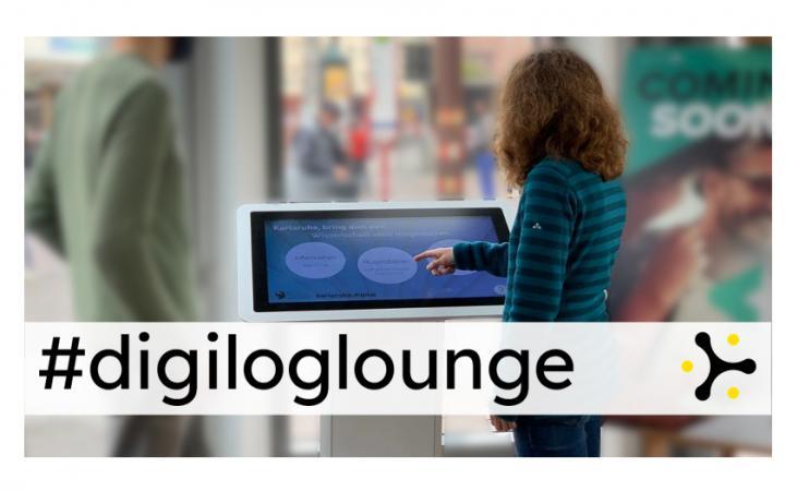 """Zwei Personen stehen an einem Panel mit Touchscreen. Über dem Bild liegt das Banner """"#digiloglounge"""""""
