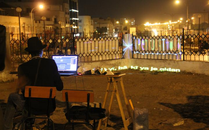 A man sits with his back to us on a laptop at a writing-room on a nocturnal terrace illuminated by street lights.