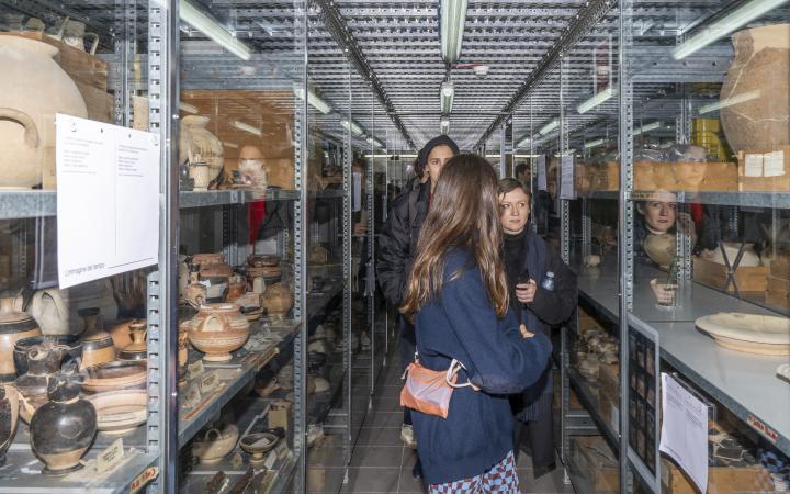 Drei Frauen stehen in einer Abstellkammer mit verschiedenen Gegenständen.