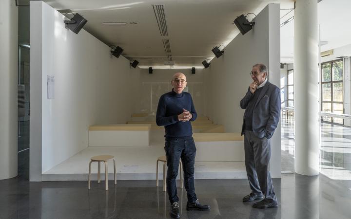 Zwei Männer stehen in einem großen hellen Raum.