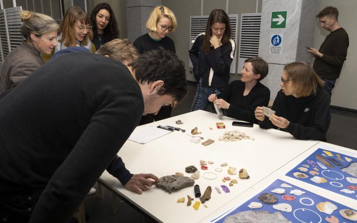 Eine Gruppe von Menschen vor einem Tisch mit verschiedenen Materialien.