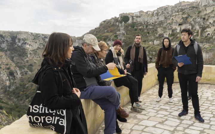 Eine Gruppe von Menschen stehen im freien vor einer bergigen Landschaft.