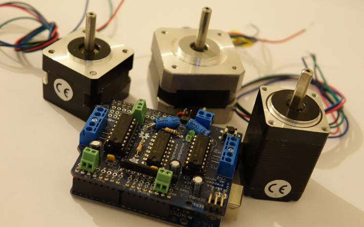 Three stepper motors and a circuit board are connected with multicolor wires.