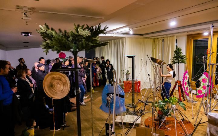 Zu sehen ist der Kulturraum Korea in Berlin während einer Performance. Auf der linken Seite stehen die BesucherInnen während auf der rechten Seite eine Performerin sich zwischen verschiedenen Soundobjekten bewegt.
