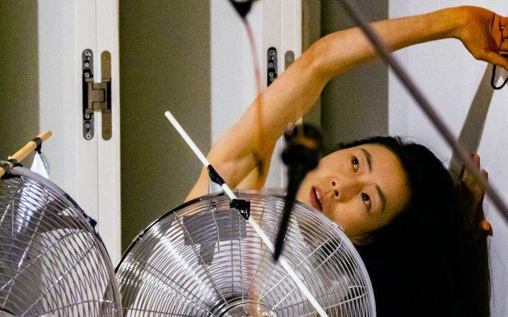 Das Foto zeigt eine koreanische Performerin die nach links gebeugt ihren Arm über ihren Kopf ausstreckt, während vor ihr ein großer silberfarbener Ventilator steht.