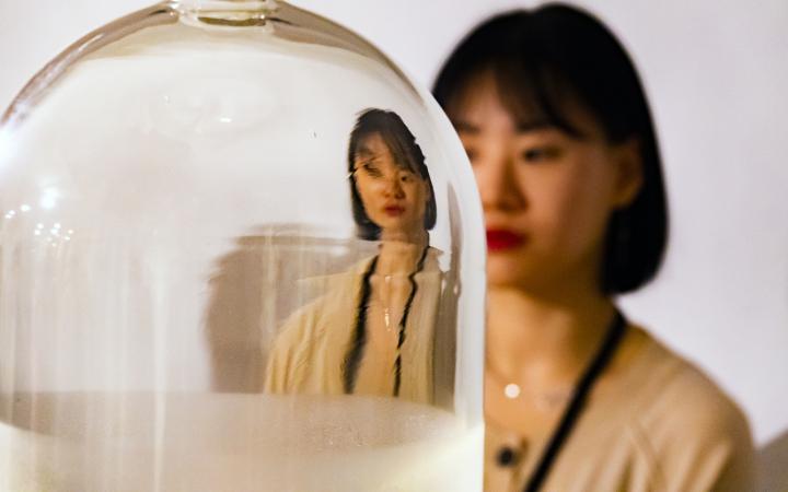 Das Foto zeigt eine Glasglocke hinter der eine koreanische Frau steht. Ihr Gesicht und Oberkörper reflektieren verzerrt in der Glasglocke.