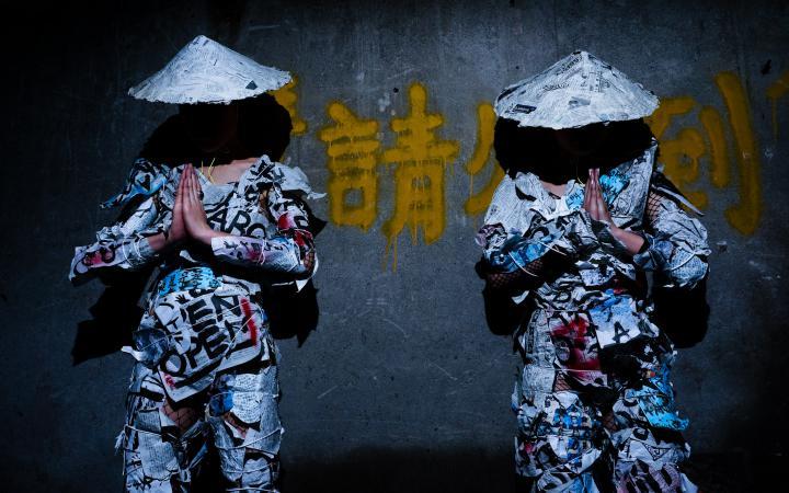 Das Duo group A vor einer grauen Wand mit gelben japanischen Schriftzeichen