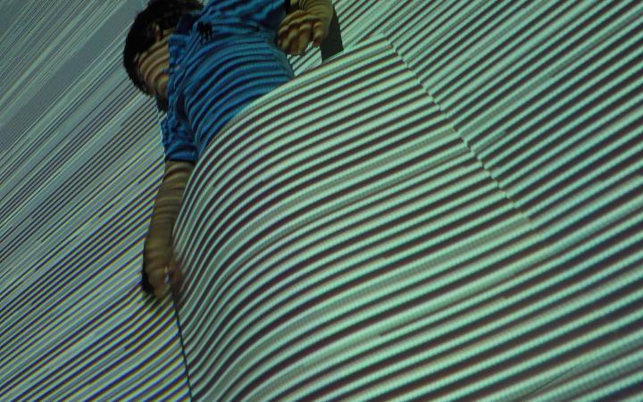 Ein Junge vor einer Projektionswand steckt in einem Bogen Papier, wodurch es aussieht als würde er von der Projektion zugedeckt.