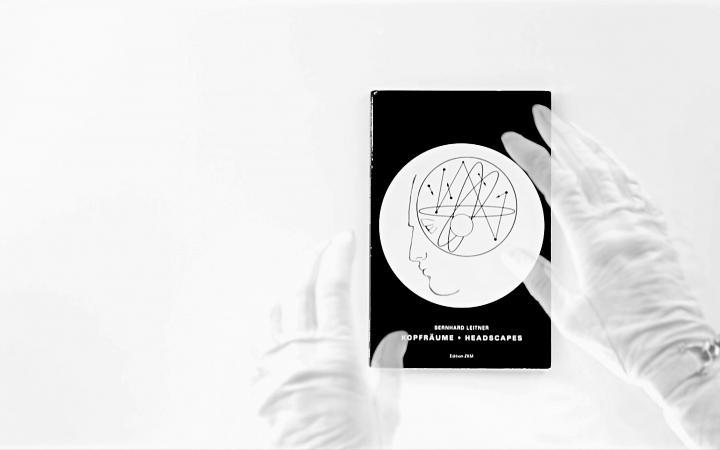 Zwei Hände in weissen Handschuhen vor einer schwarzen DVD-Hülle