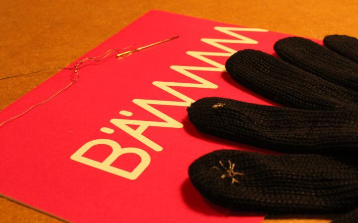 Ein Handschuh mit leitendem Faden an den Fingerspitzen liegt auf dem Tisch neben einem BÄM-Flyer