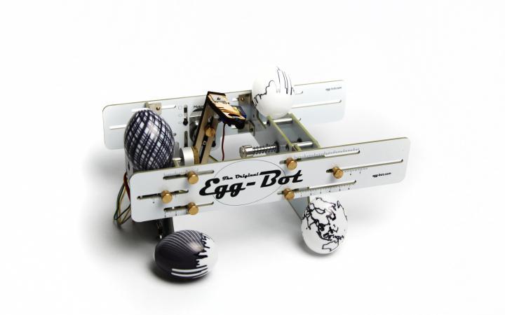Der Egg-Bot mit vier verschieden bemalten Eieren vor weißem Hintergrund