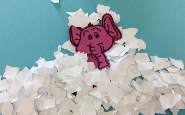 A still out of an stop motion movie with a pink elephant that is covered with shreds of paper, that make him look like he is stuck in snow.
