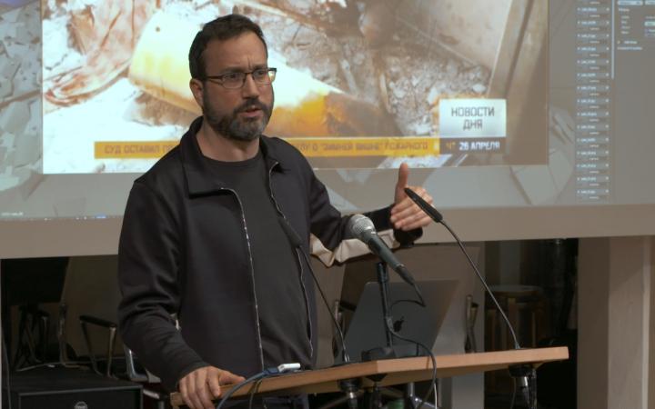 Eyal Weizman, ein Mann mit Bart und Brille hält einen Vortrag vor einer Leinwand..