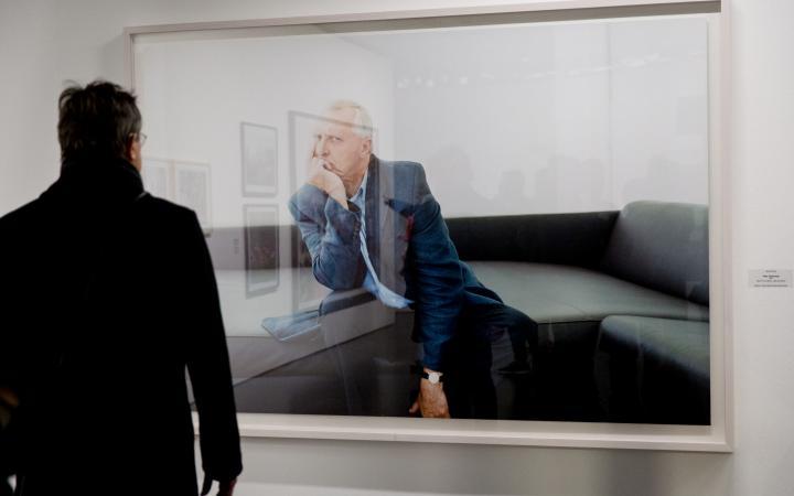 Ein Mann steht vor einer großen Fotografie