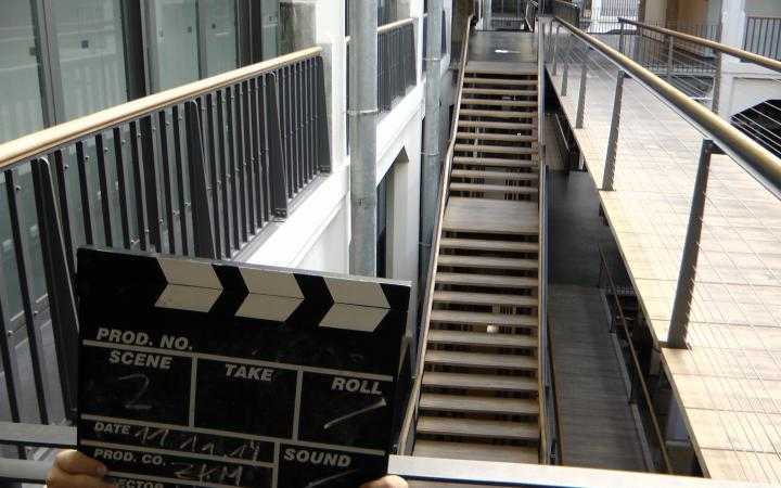 There are little hands of a child visible, they are holding a clapperboard for movies. In the background we can see stairs within the zkm.