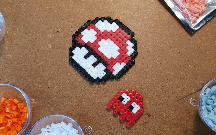 Foto von einem roten Fliegenpilz aus Super Mario und einem Geist aus Pacman – beides gebastelt aus Bügelperlen.