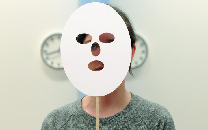 A person of undefined gender holding a white paper mask in fron of her face.