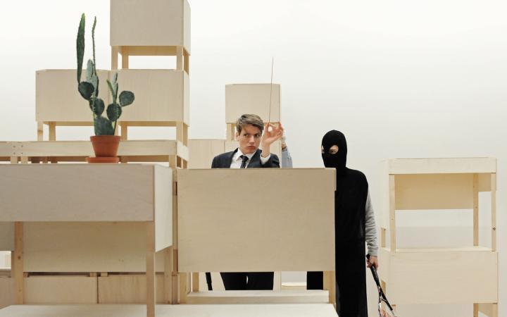 Zwischen einer Konstruktion aus hellen Möbelskulpturen aus Holz stehen zwei Personen undefinierten Geschlechts. Sie Blicken auf einen Kaktus.