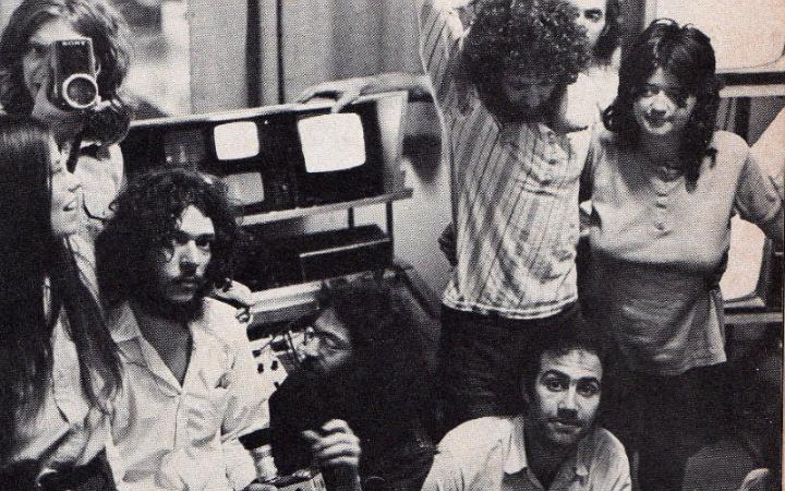 The black-and-white image shows a group of long-haired young people in front of small screens