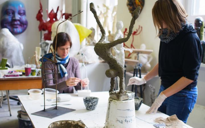 Women in an atelier are workig on slender figurines out of gesso.