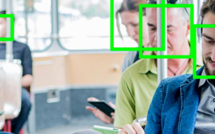 Das Foto zeigt Personen in einer Straßenbahn, die allesamt auf ihr Smartphone schauen. Über ihren Gesichtern liegt das Gesichtserkennungssymbol in neongrüner Farbe.