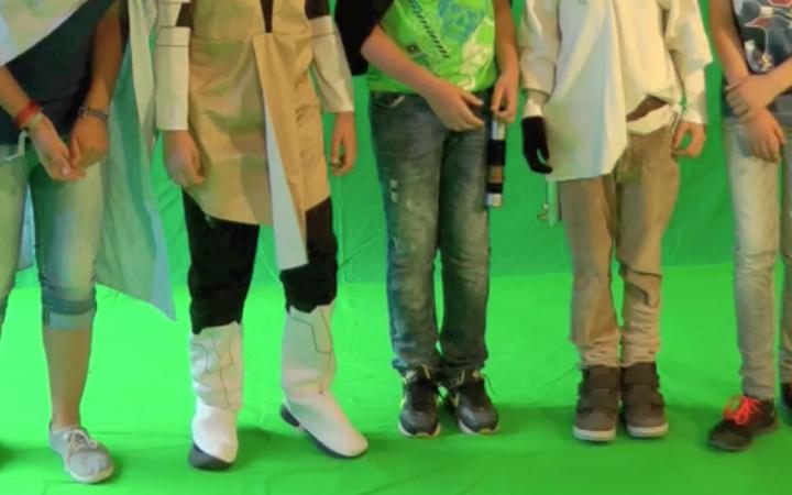 Fünf Kinder stehen nebeneinander vor einem Greenscreen - man kann nur ihre Beine sehen.