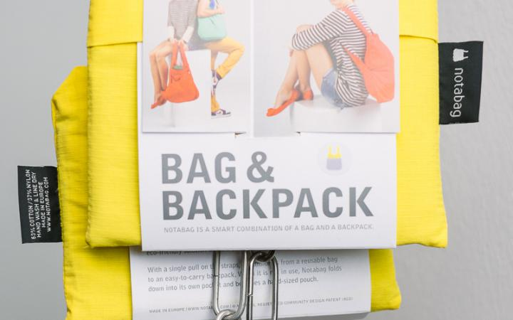A combination of bag and backpack, folding, yellow, hung up on an iron chain