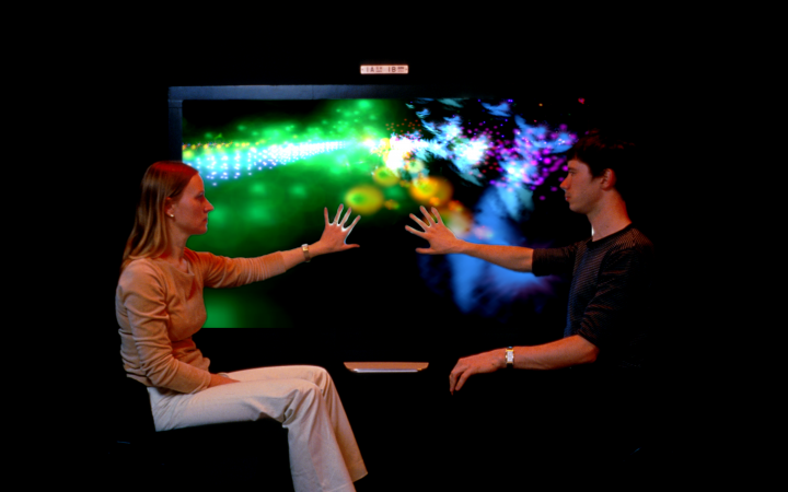 Two people touching an illuminated screen