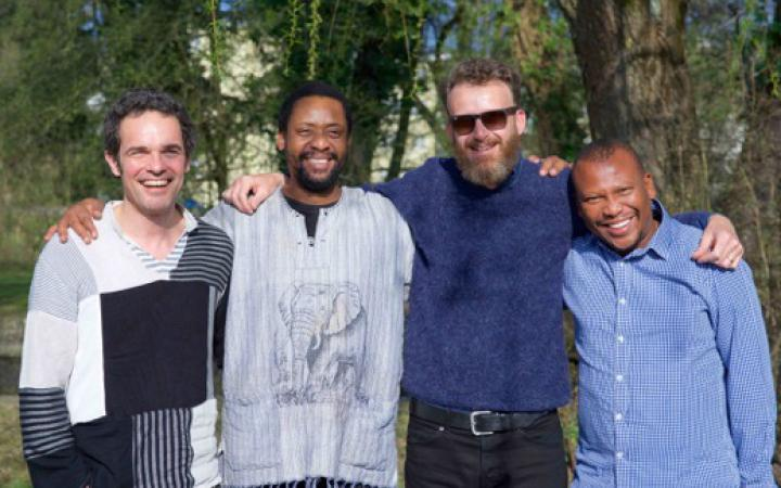 The picture shows the four radiant members of Bänz Oester & The Rainmakers