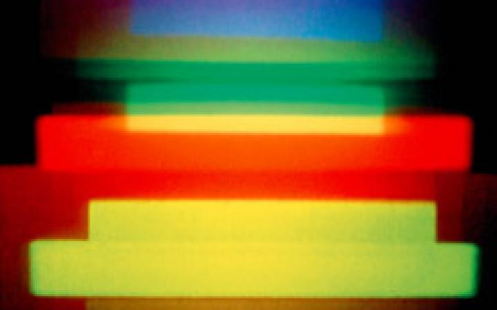 A holographic image by Dieter Jung. Red, blue, green and yellow horizontal stripes on a dark background.