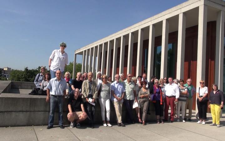 Personen stehen vor einem Gebäude
