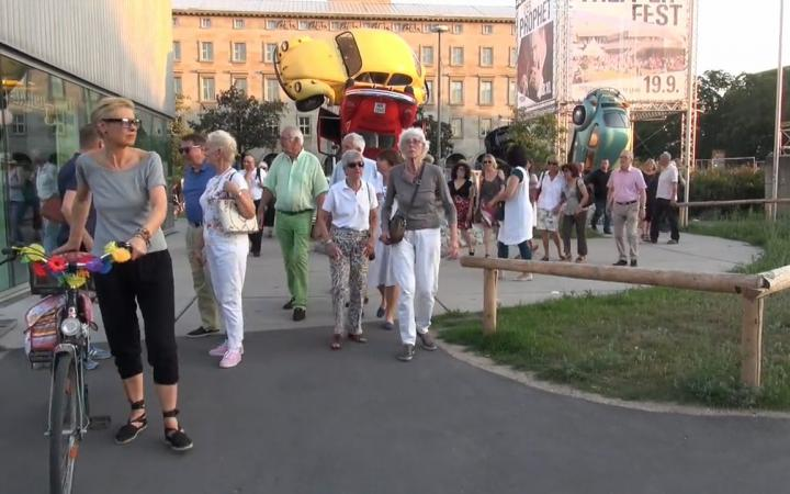 Mehrere Personen laufen vor aufeinandergestapelten VW-Käfern