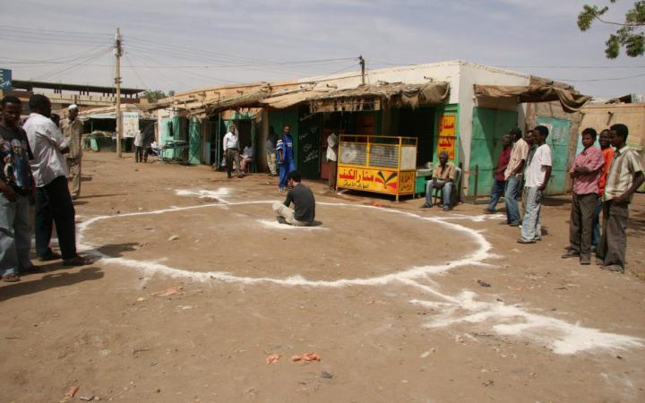 Ein Mann sitzt auf einem sandigen Boden in einem weißen Kreis
