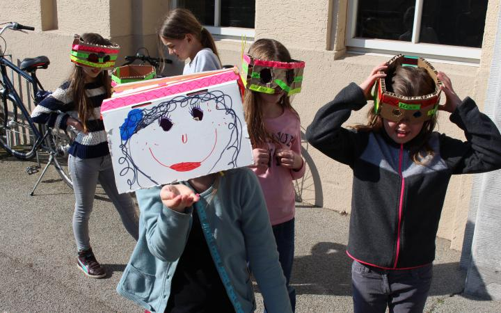 Eine Gruppe Mädchen, die sich aus alltäglichen Gegenständen Masken gebastelt haben stehen vor dem Eingang zum ZKM Gebäude.