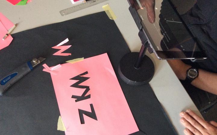 Auf einem Tisch ist das Equipment aufgebaut, welches für Legetrick benötigt wird. Außerdem ein Rosafarbenes Blatt Papier aus dem die Buchstaben ZKM ausgeschnitten wurden.