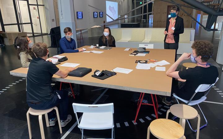Studierende der Filmuniversität Babelsberg KONRAD WOLF sitzen in der Ausstellungs »Critical Zones« an einem Holztisch