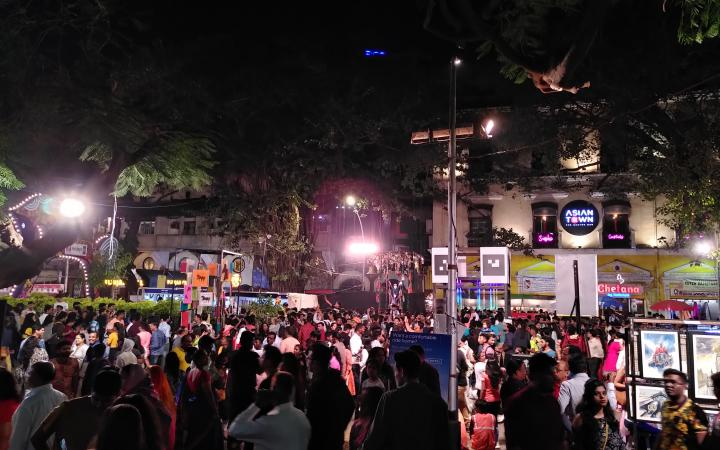 Viele Menschen auf einer Straße bei Nacht versammelt im Rahmen des Kala Ghoda Festivals in Mumbai.
