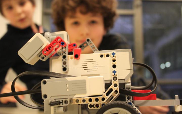 Im Vordergrund steht ein Lego-Roboter und zwei Jungen sitzen im Hintergrund. Die Gesicher der Kinder sind nur unscharf zu erkennen.