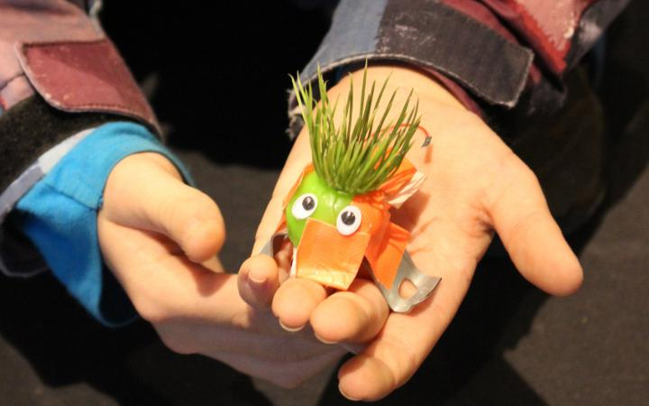 A kid is holding a little e-bug in his hands for the photo. The e-bug has fake lawn as hair and his body is made of metal and tape