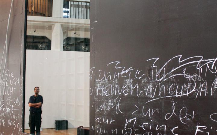 Eine beschriebene schwarze Wand mit einem Spiegel