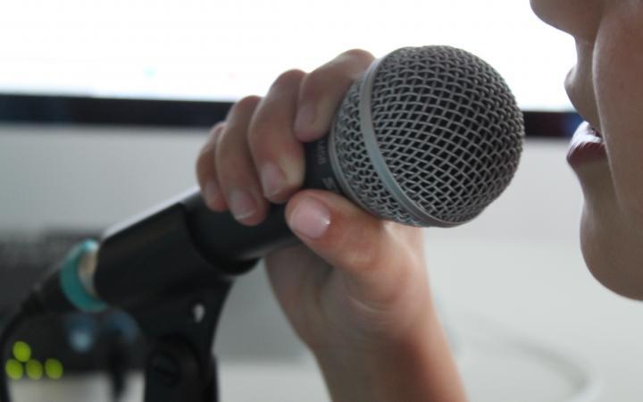 Ein Jugendlicher spricht in ein Mikrofon, das er sich vor den Mund hält.