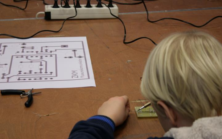 A boy is working on a circuit board with a soldering iron, out of which he is buil