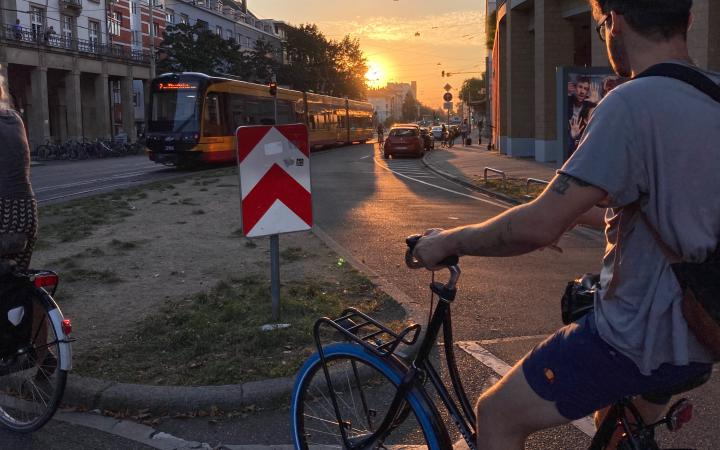 In the foreground, a young man on a bicycle is riding along a road. In front of him, the setting sun is shining and illuminating the streetcar that crosses the landscape.