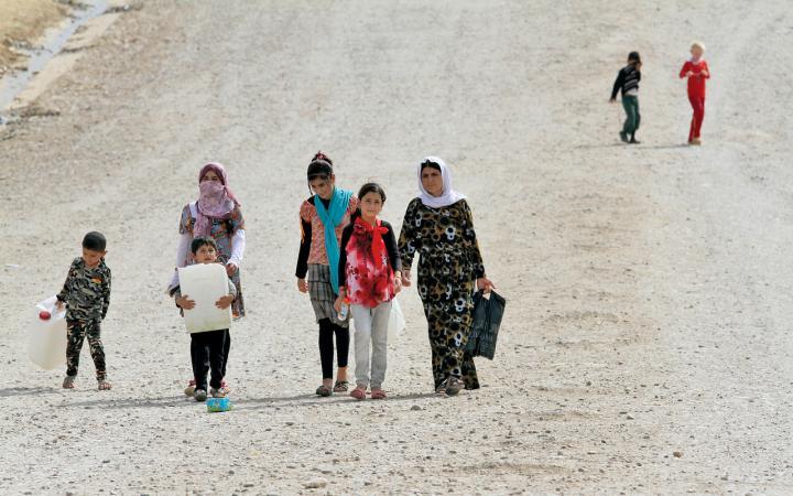 Junge verschleierte Frauen und Kinder auf einer Straße.